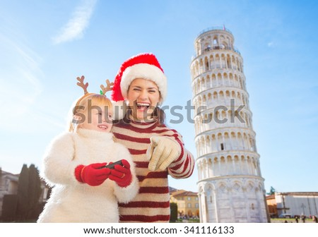 Happy mother in Christmas hat pointing in camera and daughter in funny reindeer antlers holding photo camera. Leaning Tour of Pisa, Italy in background. Exciting Christmas time travel. - stock photo