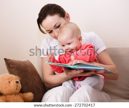 Happy mother is reading book with cute daughter - stock photo