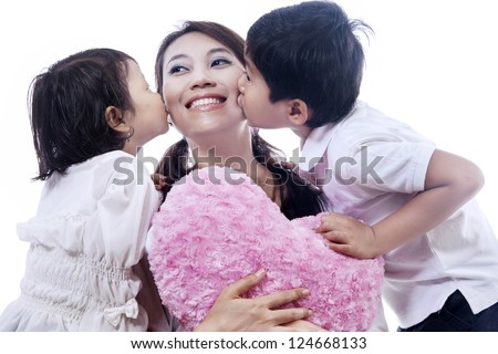Happy mother kissed by her daughter and son isolated over white background - stock photo