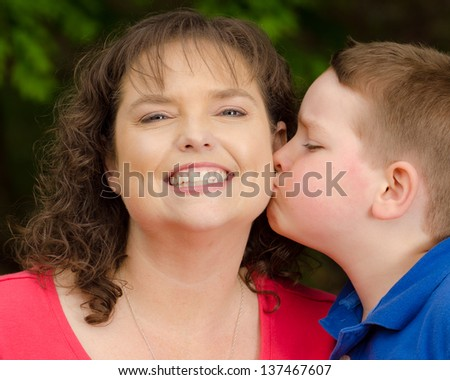 Happy mother kissed by son - stock photo