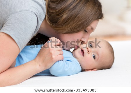 Happy mother kisses her baby while playing on white bed - stock photo