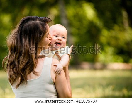 Happy mother kissing and hugging her baby - outdoor in nature - stock photo