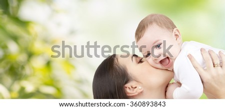 happy mother kissing baby over green background - stock photo