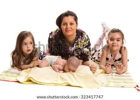 Happy mother laying  on blanket together with her three girls  - stock photo