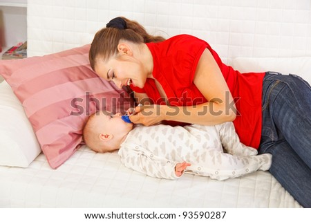 Happy mother laying on couch and giving soother to baby - stock photo