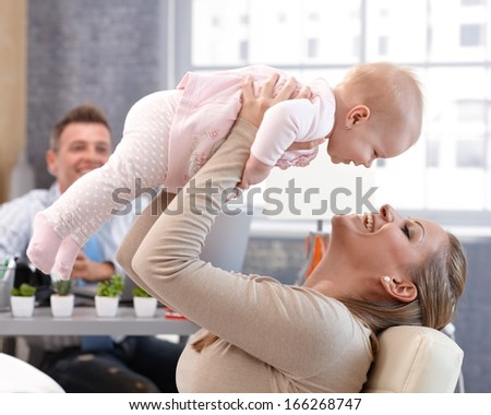 Happy mother lifting up high little baby daughter, having fun, laughing. Father watching from background. - stock photo