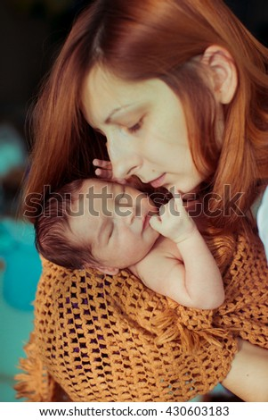 happy mother looks at her wonderful baby - stock photo