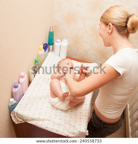Happy mother playing with her baby on the changing diaper table while hygienic procedures  - stock photo