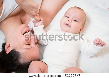 happy mother playing with her cute baby lying in bed - stock photo