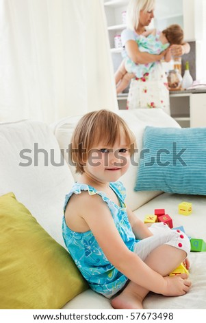 Happy mother playing with her daughters in the living room - stock photo