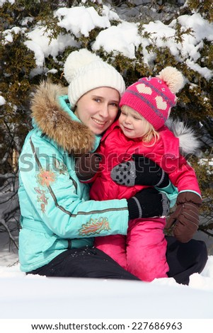 Happy mother playing with her toddler daughter in the winter park  - stock photo