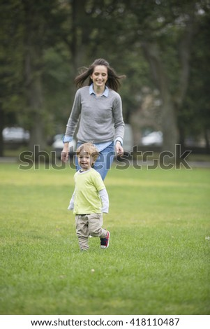 Happy Mother playing with her toddler son outdoors. Love and togetherness concept. Selective focus. - stock photo