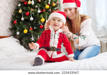 Happy mother putting Santa costume on toddler son at home - stock photo