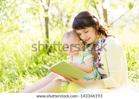 happy mother reading a book to baby in garden - stock photo