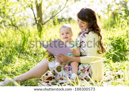 happy mother reading a book to baby outdoors - stock photo