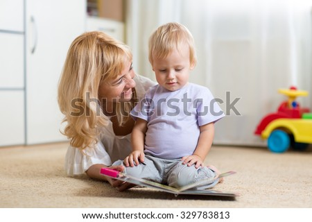 happy mother reading a book to child boy indoors - stock photo