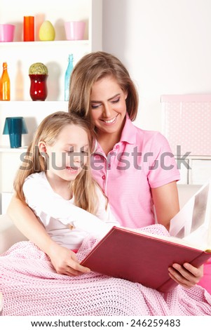 Happy mother reading book with child - stock photo