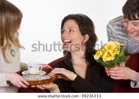 Happy mother receiving coffee and flowers on mother's day - stock photo