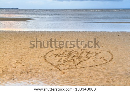 Happy Mother's Day written in a love heart, in the sand on a flat rippled beach. A calm blue sea fills the background. - stock photo