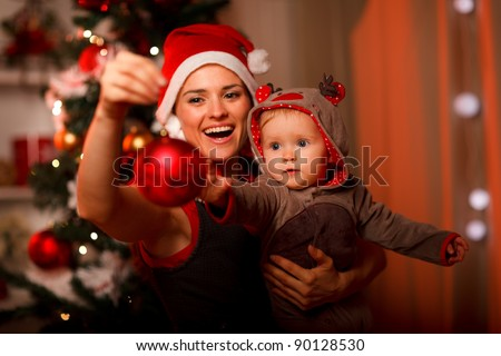 Happy mother showing Christmas ball  to baby near Christmas tree - stock photo
