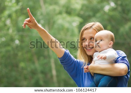 Happy mother showing something to her daugher - stock photo