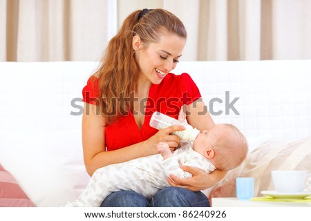 Happy mother sitting on sofa and feeding baby - stock photo