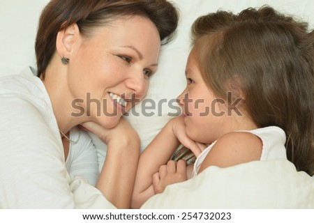 Happy mother spending time with little daughter in bed - stock photo