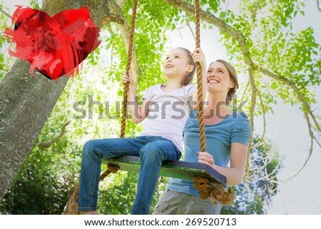 Happy mother swinging daughter at park against heart - stock photo