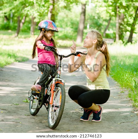 Happy mother talking with her daughter smiling, which teaches to ride a bike - stock photo