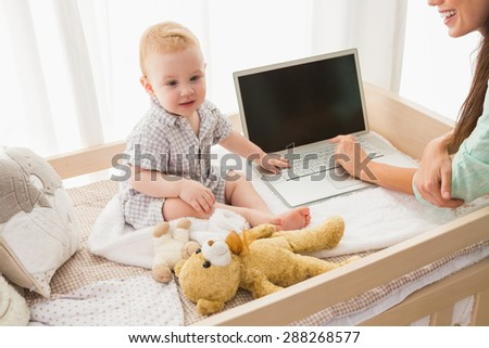 Happy mother using laptop with her baby boy at home in bedroom - stock photo
