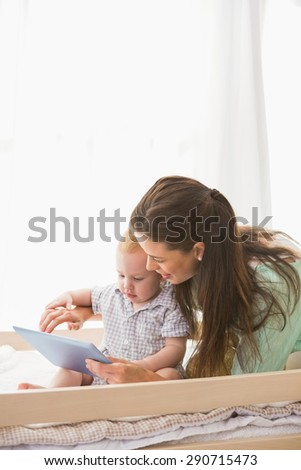 Happy mother using tablet with his baby boy at home in bedroom - stock photo