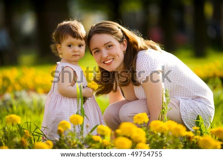 Happy mother walking with daughter in park outdoors - stock photo