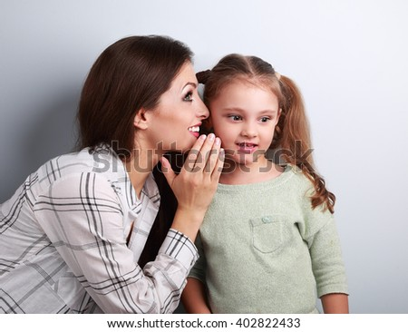 Happy mother whispering the secret to her cute kid girl in ear with fun face on blue background - stock photo