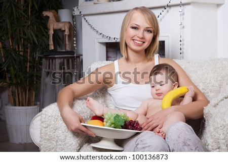 happy mother with a baby eating fruit - stock photo