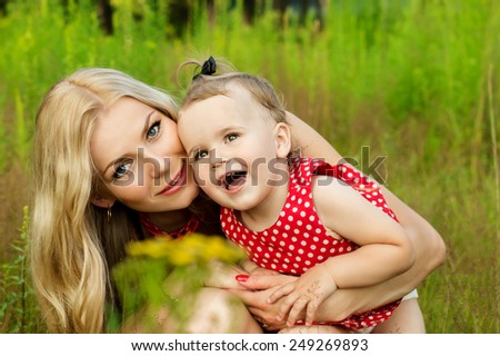 Happy mother with a baby on nature background - stock photo