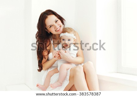 Happy mother with baby at home in white room near window - stock photo