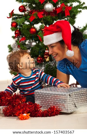 Happy mother with baby boy celebrating Christmas - stock photo