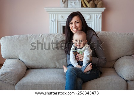 Happy mother with baby boy on coah - stock photo