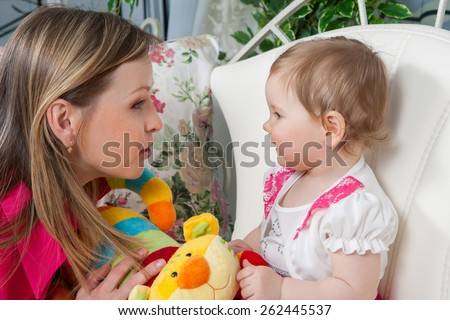 Happy mother with  baby daughter in a beautiful dress at home near the fireplace. Mom tells daughter story. Baby listens with delight. - stock photo