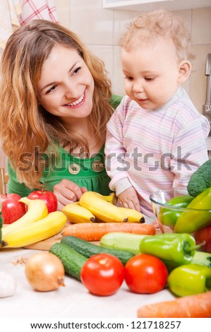 Happy mother with baby daughter preparing vegetable salad - stock photo