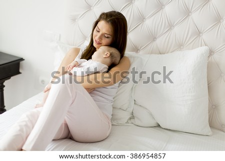 Happy mother with baby on bed - stock photo