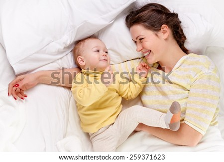 happy mother with baby on white bed, shot from above - stock photo