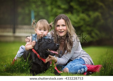 Happy mother with baby playing with dog in green field - stock photo