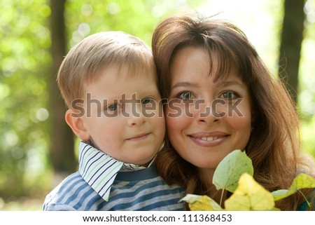 Happy mother with boy   against nature - stock photo