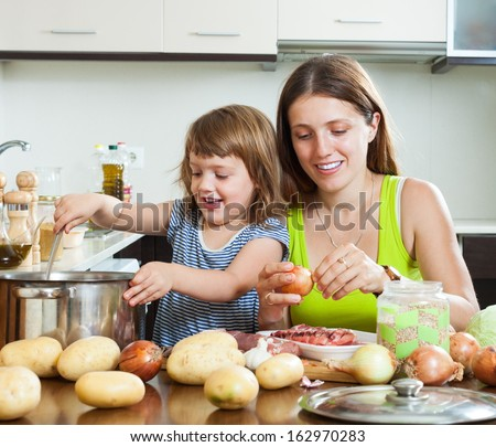 Happy mother with daughter making soup together at domestic kitchen - stock photo