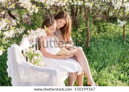 Happy mother with daughter with book in spring garden - stock photo