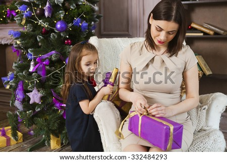 Happy mother with daughter wrapping Christmas gifts at home near the Christmas tree - stock photo