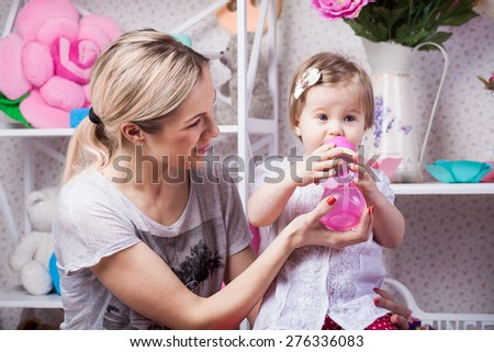 Happy mother with drinking water daughter - stock photo