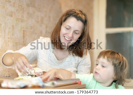 Happy mother with girl foiling fish at kitchen. Focus on woman - stock photo