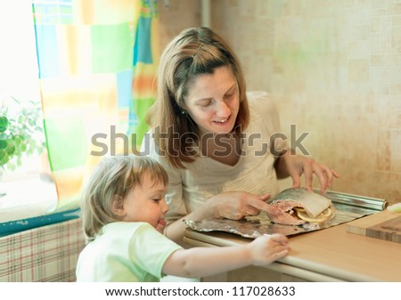 Happy mother with girl foiling salmon at kitchen - stock photo